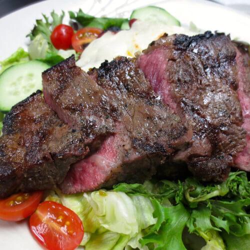 sliced steak served over salad